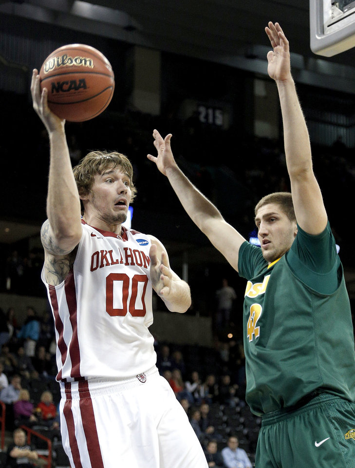 Photo - Oklahoma's Ryan Spangler (00) looks to pass the ball around North Dakota State's Marshall Bjorklund (42) NCAA men's basketball tournament game between the University of Oklahoma and North Dakota State at the Spokane Arena in Spokane, Wash., Thursday, March 20, 2014. Photo by Sarah Phipps, The Oklahoman