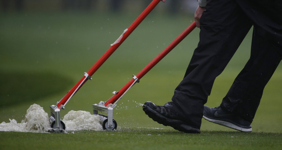 Photo - Members of the grounds crew push water off the 12th fairway during the second round of the PGA Championship golf tournament at Valhalla Golf Club on Friday, Aug. 8, 2014, in Louisville, Ky. (AP Photo/Mike Groll)