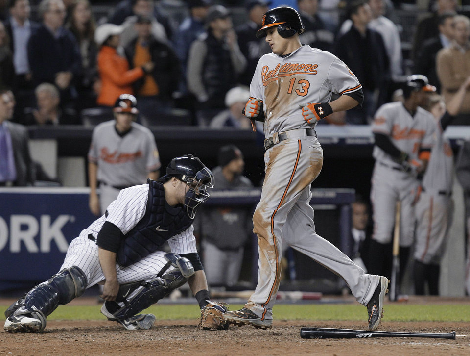 Photo -   Baltimore Orioles' Manny Machado (13) runs past New York Yankees catcher Russell Martin as he scores on a double by J.J. Hardy during the 13 inning of Game 4 of the American League division baseball series Thursday, Oct. 11, 2012, in New York. The Orioles won 2-1. (AP Photo/Kathy Willens)