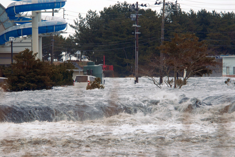 Photo - The area is flooded by tsunami in Iwaki, Fukushima Prefecture (state) as Japan was struck by a magnitude 8.9 earthquake off its northeastern coast Friday, March 11, 2011. (AP Photo/Kyodo News)