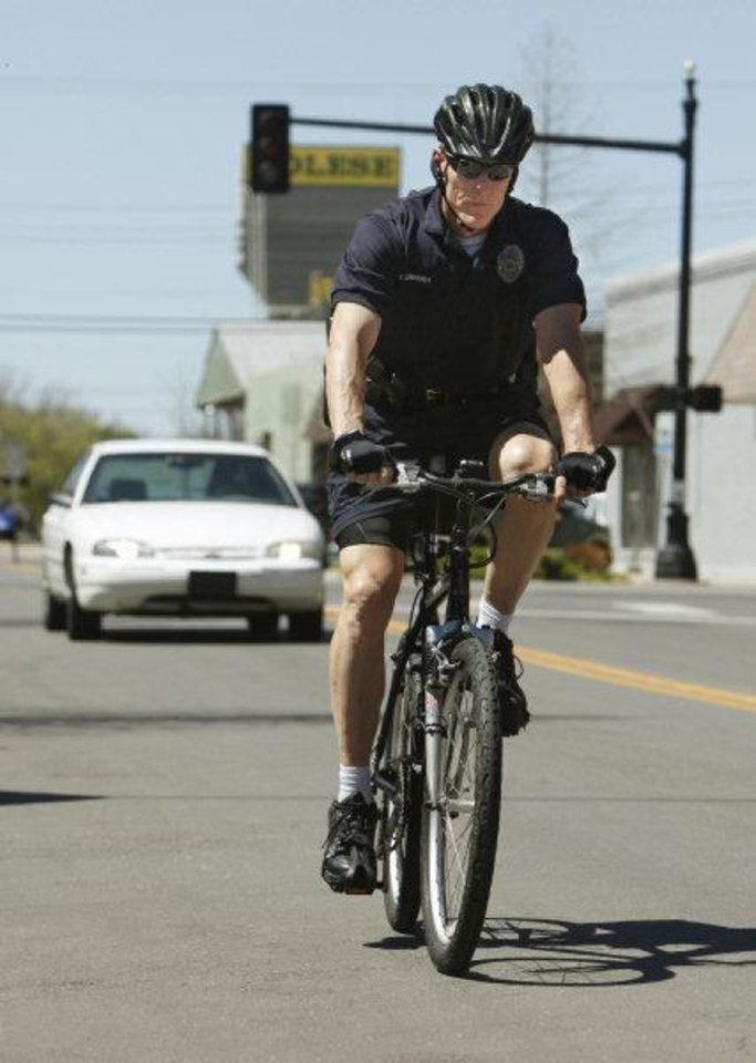 Edmond police Lt. Chuck Linhardt rides his bicycle in downtown Edmond. Linhardt is one of eight bicycle officers who will help promote amendments to Edmond\'s bicycle ordinance. PHOTO BY PAUL HELLSTERN, THE OKLAHOMAN PAUL HELLSTERN - THE OKLAHOMAN