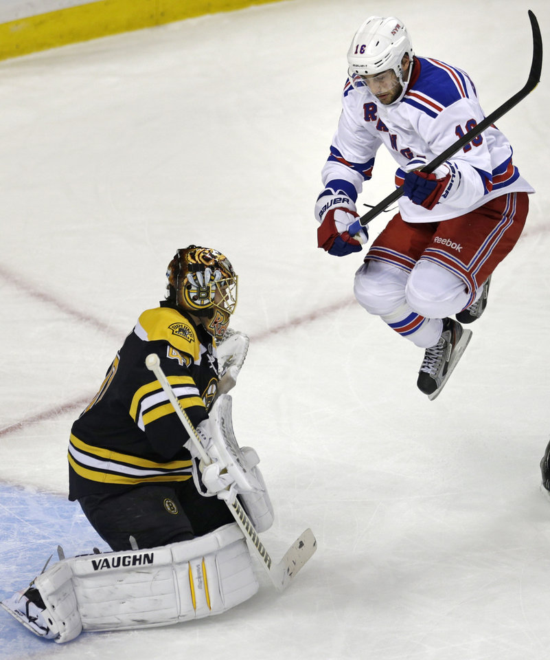 Photo - New York Rangers center Derick Brassard (16) jumps out of the way of a teammate's shot as Boston Bruins goalie Tuukka Rask, left, makes a save during the first period in Game 1 of an NHL hockey playoffs Eastern Conference semifinal game in Boston, Thursday, May 16, 2013. (AP Photo/Charles Krupa)