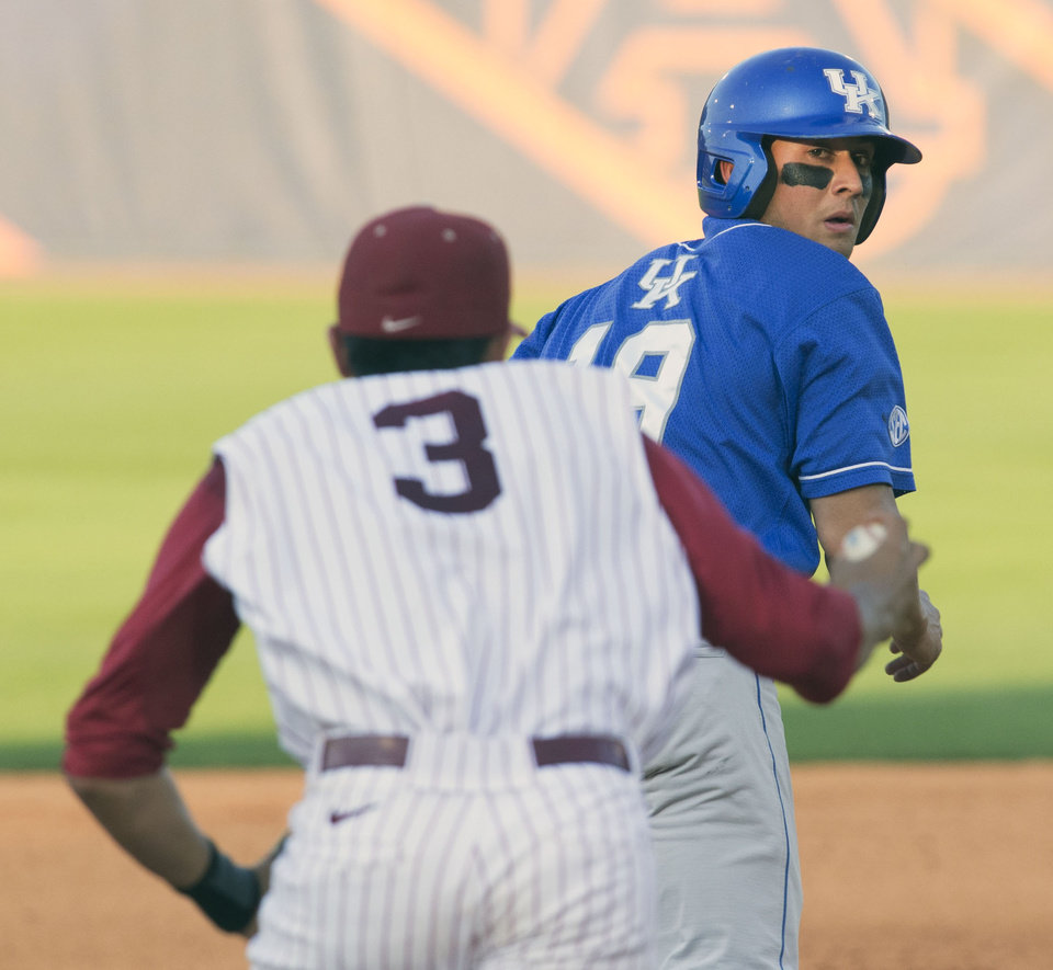 Photo - Kentucky's Austin Cousino looks back at a charging Alabama's Daniel Cucjen as he is caught between second and third during the Southeastern Conference NCAA college baseball tournament, Tuesday, May 20, 2014, in Hoover, Ala. (AP Photo/Hal Yeager)