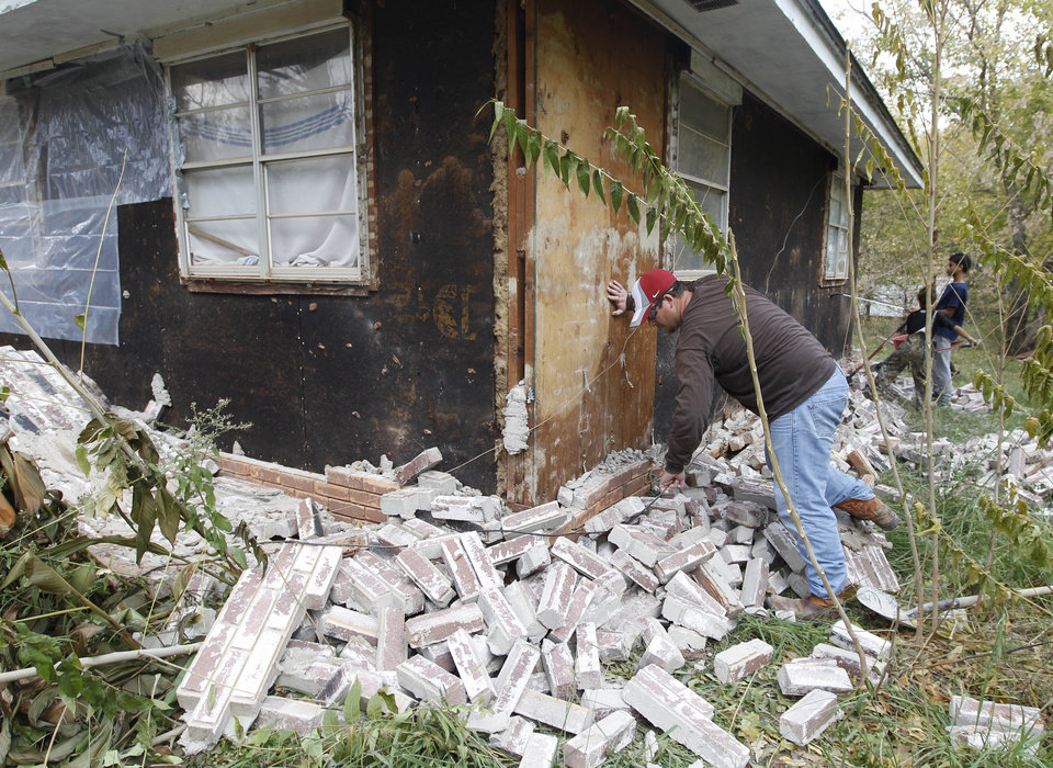 Photo - FILE - In this Nov, 6, 2011 file photo, Chad Devereaux examines bricks that fell from three sides of his in-laws home in Sparks, Okla., following two earthquakes that hit the area in less than 24 hours. A study published Thursday, July 3, 2014 by the journal Science explains how just four wells forcing massive amounts of drilling wastewater into the ground are probably causing quakes in Oklahoma. The wells seem to have triggered more than 100 small-to-medium earthquakes in the past five years, according to a study. (AP Photo/Sue Ogrocki, File)