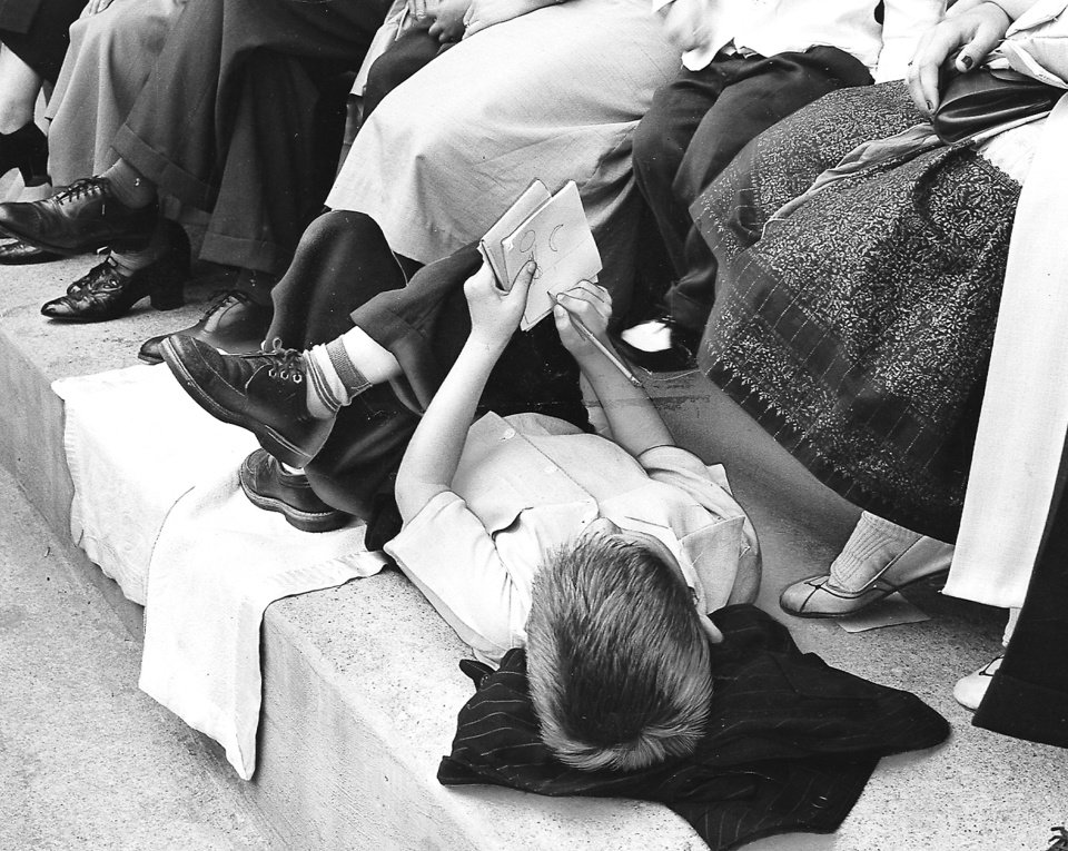 Photo - A pen and paper kept this young boy occupied as he lay at his parents' feet during the 1956 Oklahoma City crusade with the Rev. Billy Graham. Staff Photo by Dick Peterson (Original photo taken 06/3/56, ran 06/05/56 TIMES)