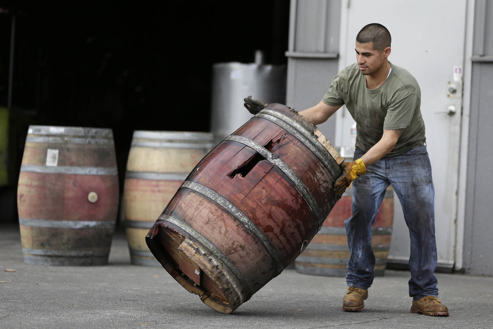 Photo - A worker removes an earthquake-damaged wine barrel from Napa Barrel Care Monday, Aug. 25, 2014, in Napa, Calif. A powerful earthquake that struck the heart of California's wine country caught many people sound asleep, sending dressers, mirrors and pictures crashing down around them and toppling wine bottles in vineyards around the region. The magnitude-6.0 quake struck at 3:20 a.m. PDT Sunday near the city of Napa. (AP Photo/Eric Risberg)