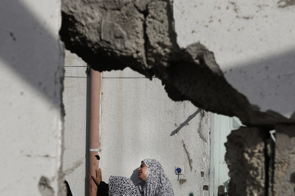 Photo - A Palestinian relative of the Abu Wahdan family cries outside a damaged house in the Jebaliya refugee camp that was hit by an Israeli strike that killed several members of the family, in the northern Gaza Strip, Sunday, Aug. 3, 2014. Jamila, 55, Hatem, 57, and Sanwara  Abu Wahdan, 27, were killed at the house after the extended family of more than 40 people had sought refuge in Jebaliya from shelling elsewhere. (AP Photo/Lefteris Pitarakis)