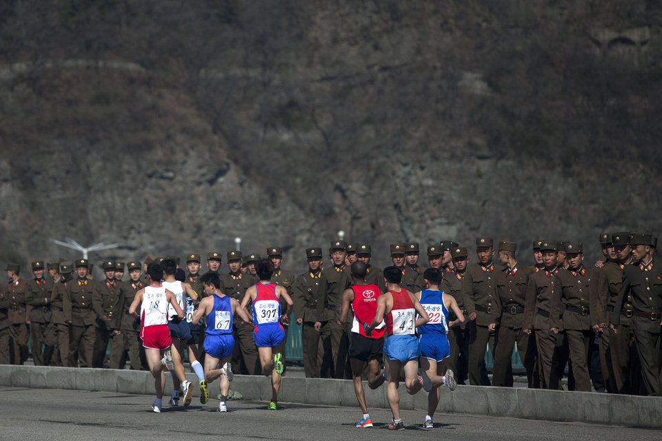 Photo - FILE - In this April 14, 2013 file photo, marathon runners pass by a long row of North Korean soldiers as they cross a bridge in Pyongyang as North Korea hosts the 26th Mangyongdae Prize Marathon to mark the birthday of the late leader Kim Il Sung on April 15. For the first time ever, North Korea is opening up the streets of its capital to runner-tourists for the annual Pyongyang marathon, undoubtedly one of the most exotic feathers in any runner's cap. Tourism companies say they have been inundated by requests to sign up for the April 13, 2014 event, which this year will include amateur runners from around the world. (AP Photo/David Guttenfelder, File)