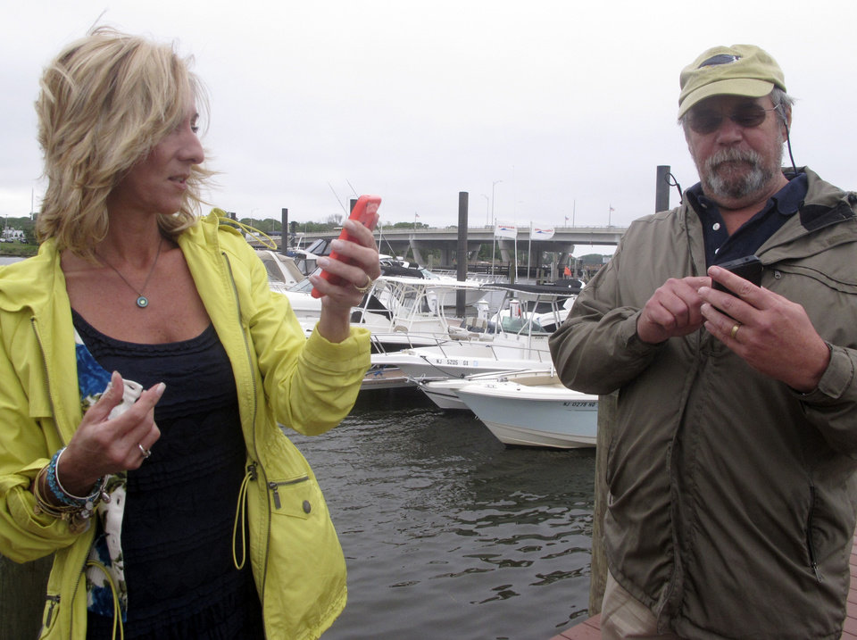 Photo - In this photo taken on May 28, 2014, Helen Henderson, a project manager for the American Littoral Society, left, and Capt. Walt Nadolny, right, check current pollution reports using a new smart phone app developed for the group that lets people quickly and easily report water pollution or other marine environmental problems to authorities at a marina in Brick, N.J. The project was paid for by a $325,000 federal grant that came from fines levied on water polluters. (AP Photo/Wayne Parry)