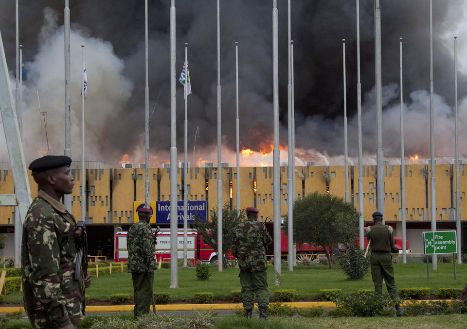FILE - In this Wednesday, Aug. 7, 2013 file photo, police stand guard as fire engulfs the international arrivals unit of the Jomo Kenyatta International Airport, in Nairobi, Kenya.   Putting that disaster in the past , Kenya Airways� chief executive Titus Naikuni is predicting an exciting couple of years for African air travel, with new Boeing Dreamliners, the opening of a new terminal and, on the horizon, Kenya's first direct flights to the United States.(AP Photo/Sayyid Azim, File)
