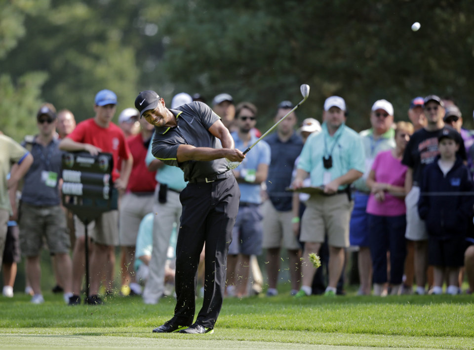 Photo - Tiger Woods hits his approach shot to the 11th green during the second round of the Bridgestone Invitational golf tournament Friday, Aug. 1, 2014, at Firestone Country Club in Akron, Ohio. (AP Photo/Mark Duncan)