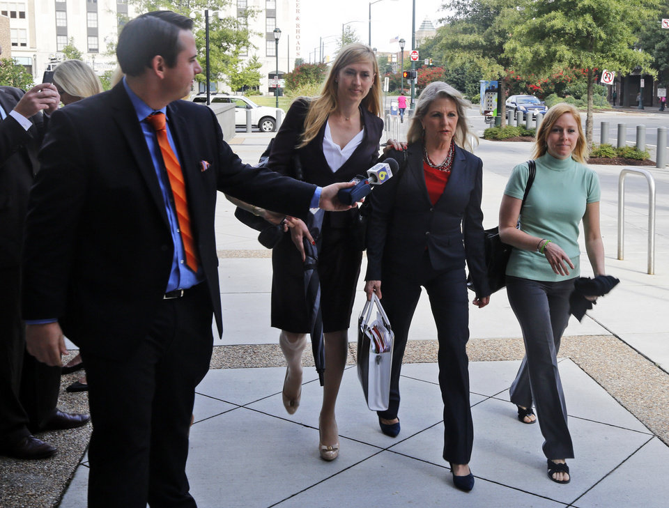 Photo - A reporter asks former Virginia first lady, Maureen  McDonnell, second from right, a question as she arrives at federal court with  daughter Cailin Young, right, and her attorney Heather Martin, second from left, Tuesday, Aug. 19, 2014, in Richmond, Va. The McDonnells are presenting the second day of his defense on corruption charges. (AP Photo/Steve Helber)