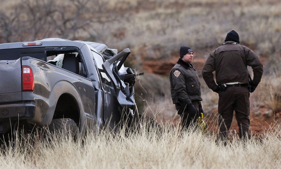 Photo - OHP investigators stand near the wreckage of a 2011 Ford pickup truck after it was pulled from a ravine where it landed after the driver ran off a two lane blacktop road east of Dill City.  This truck was driven by suspect Quentin Lee Johnson, 27 of Sentinel. Two officers died in a separate crash as they pursued this vehicle near Dill City. A Burns Flat police officer and an undersheriff for the Washita County Sheriff's Department died in a car crash on Thursday, Jan. 23, 2014, at a rural intersection about one mile south of Dill City.  According to OHP spokesman, the lawmen became involved in a high-speed pursuit  when a Washita County man fled as the undersheriff approached him to serve a felony warrant Thursday morning.  That same suspect died about the same time in another crash about three miles east of the location where the law officers collided. Dill City is located 75 miles west of Oklahoma City. Photo by Jim Beckel, The Oklahoman