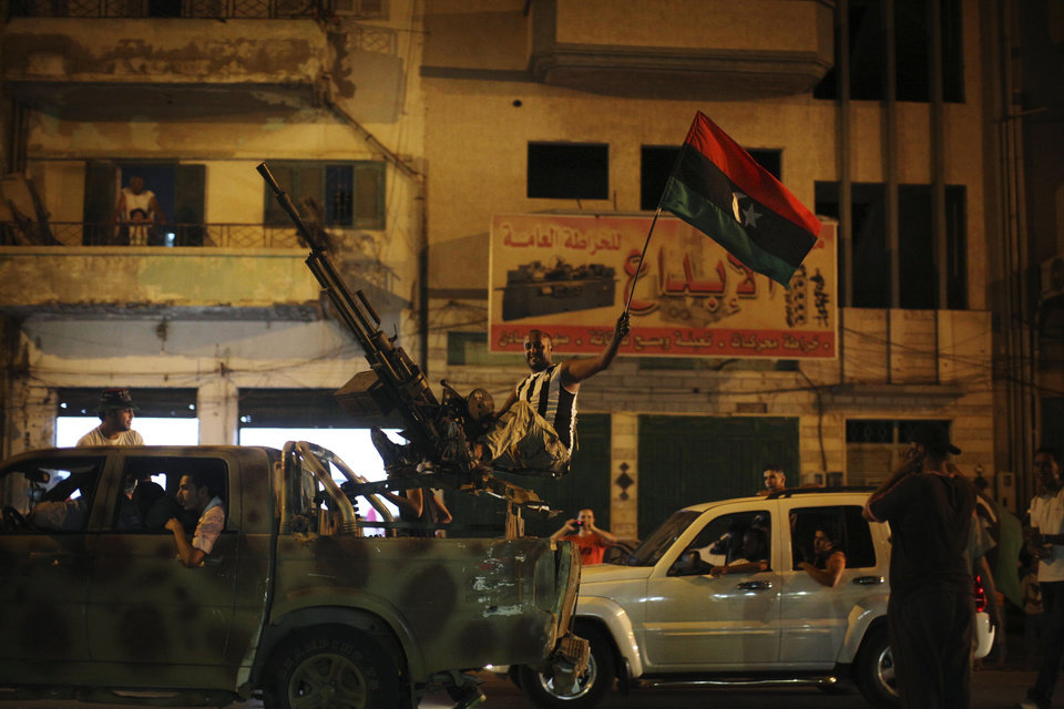 A rebel fighter, over an anti-aircraft machine gun, celebrates the capture in Tripoli of Moammar Gadhafi's son and one-time heir apparent, Seif al-Islam, at the rebel-held town of Benghazi, Libya, early Monday, Aug. 22, 2011. Libyan rebels raced into Tripoli in a lightning advance Sunday that met little resistance as Gadhafi's defenders melted away and his 42-year rule appeared to rapidly crumble. (AP Photo/Alexandre Meneghini)