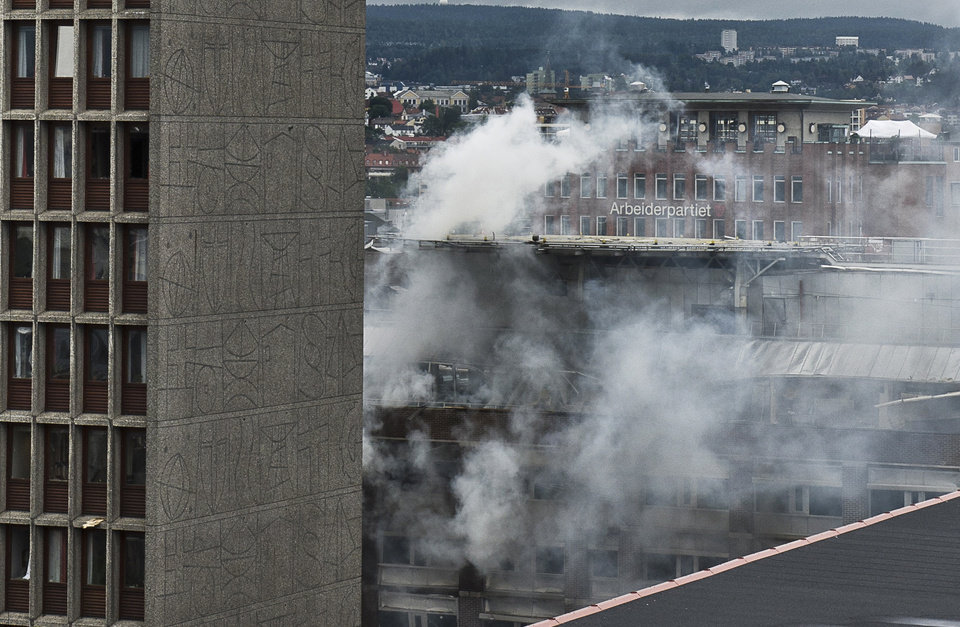 Photo - Smoke rises from buildings in Oslo, Norway, at the scene of a large explosion which tore apart several buildings Friday July 22, 2011. A loud explosion shattered windows Friday in several buildings including the government headquarters in Oslo which includes the prime minister's office, injuring several people.  Prime Minister Jens Stoltenberg is safe, government spokeswoman Camilla Ryste told The Associated Press.  The cause of the blast is not yet known. (AP PHOTO / Aleksander Andersen, Scanpix) NORWAY OUT  ORG XMIT: LON821