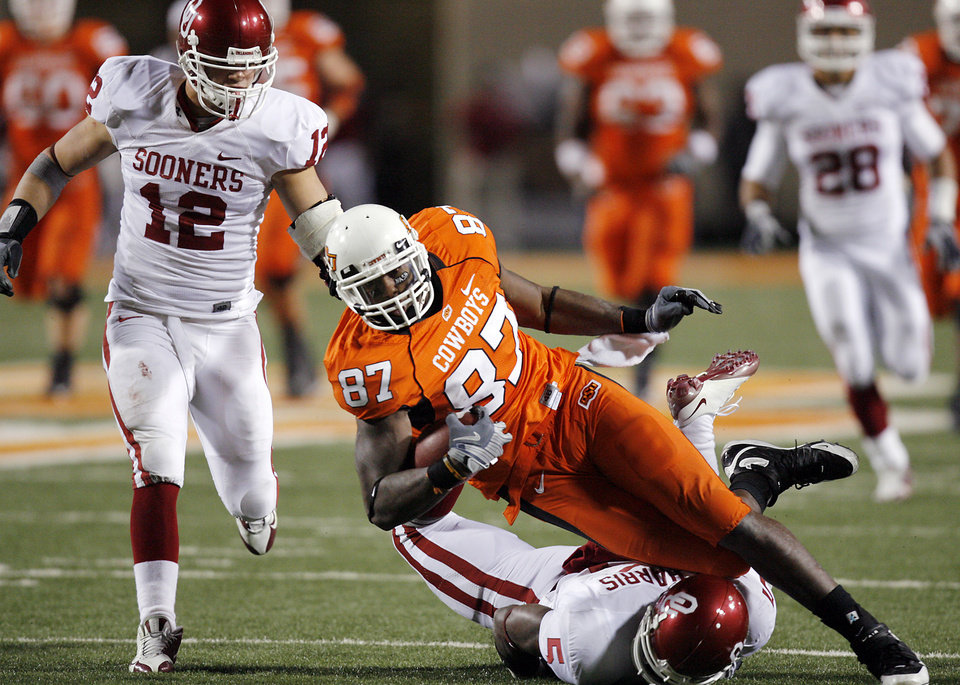 Oklahoma State's Brandon Pettigrew (87) is brought down by Oklahoma's Autin Box (12) and Nic Harris (5) during the second half of the college football game between the University of Oklahoma Sooners (OU) and Oklahoma State University Cowboys (OSU) at Boone Pickens Stadium on Saturday, Nov. 29, 2008, in Stillwater, Okla. STAFF PHOTO BY CHRIS LANDSBERGER