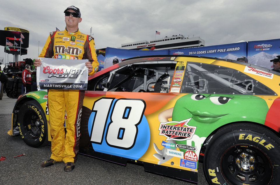 Photo - Kyle Busch poses for photos after winning the pole for Sunday's NASCAR Sprint Cup Series auto race at Martinsville Speedway in Martinsville, Va., Friday, March 28, 2014. (AP Photo/Mike McCarn)
