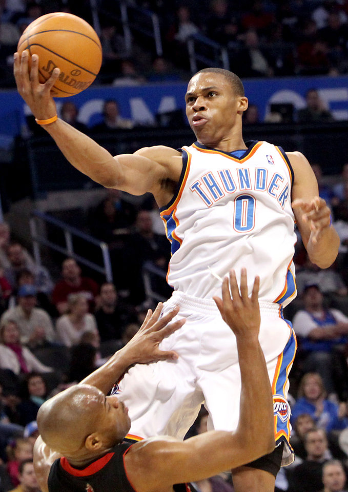 Photo - Oklahoma City's Russell Westbrook puts up a shot over Toronto's Jarrett Jack  during their NBA basketball game at the Ford Center in Oklahoma City on Sunday, Feb. 28, 2010. The Thunder beat the Raptors 119-99. Photo by John Clanton, The Oklahoman ORG XMIT: KOD