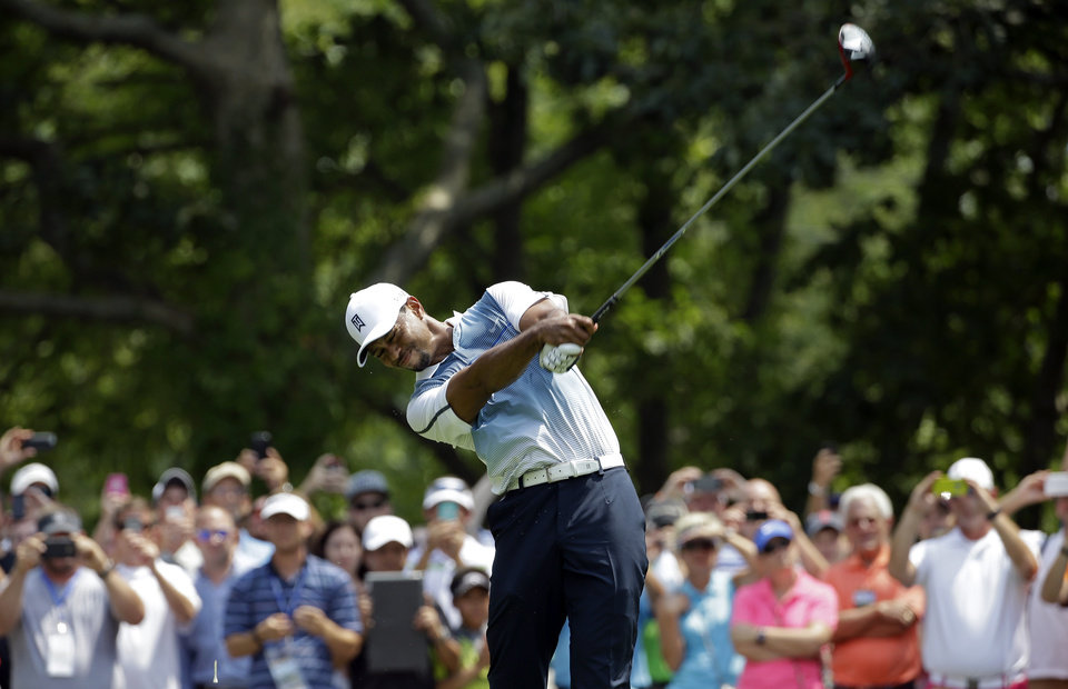 Photo - Tiger Woods hits his tee shot on the second hole during a practice round for the PGA Championship golf tournament at Valhalla Golf Club on Wednesday, Aug. 6, 2014, in Louisville, Ky. The tournament is set to begin on Thursday. (AP Photo/David J. Phillip)
