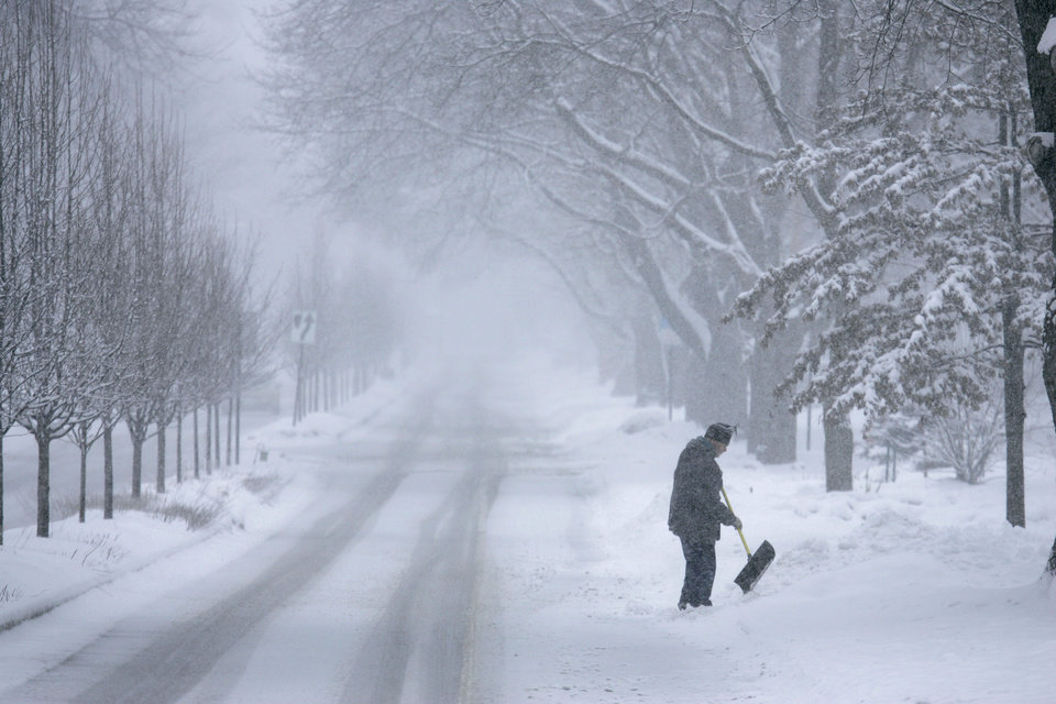 Photo - John Baer of Elgin, Ill.  finishes shoveling half of his driveway on Wing Park Ave. during a snow storm in the suburbs of Chicago, Ill. on Tuesday, March 5, 2013. (AP Photo/Daily Herald, Brian Hill)