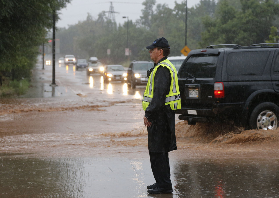 Photo - A police officer blocks traffic on a closed road following overnight flash flooding in the area, in Boulder, Colo., Thursday, Sept 12, 2013.  The widespread high waters are keeping search and rescue teams from reaching stranded residents and motorists in Boulder and nearby mountain communities as heavy rains hammered northern Colorado. (AP Photo/Brennan Linsley)
