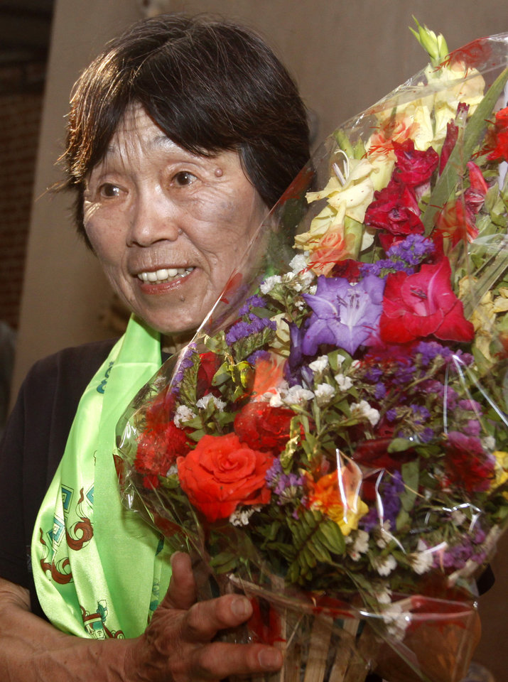 Photo -   Oldest woman climber of Mount Everest, Tamae Watanabe of Japan, holds a bouquet of flowers after arriving in Katmandu, Nepal, Friday, May 25, 2012. Watanabe, 73, has made history by becoming the oldest woman to scale the world's highest mountain, Mount Everest, bettering a record, she herself set a decade ago. (AP Photo/Binod Joshi)