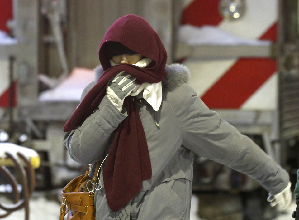 Photo - A woman walks briskly as she arrives at the La Salle Street commuter rail station with temperatures well below zero and wind chills expected to reach 40 to 50 below, Monday, Jan. 6, 2014, in Chicago. (AP Photo/Charles Rex Arbogast)