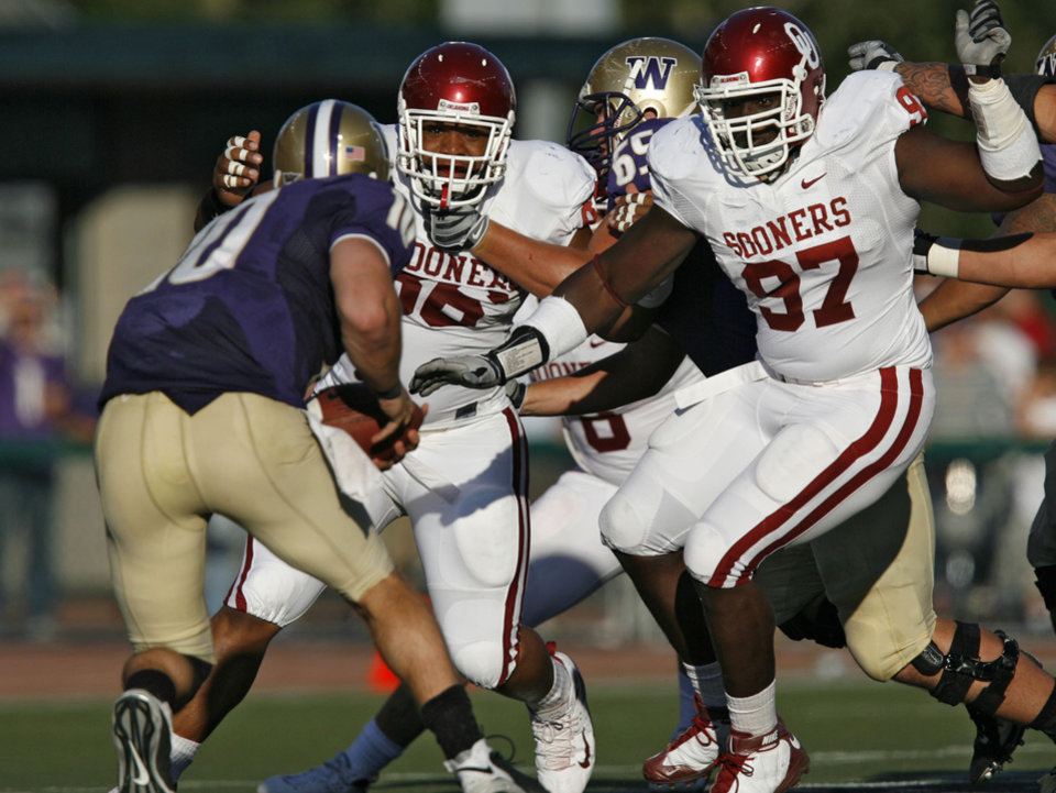 Photo - Oklahoma's DeMarcus Granger (96) and Cory Bennett (97) come after Washington quarterback Jake Locker (10) during the first half of the college football game between the University of Oklahoma Sooners (OU) and the University of Washington Huskies (UW) at Husky Stadium on Saturday, Sep. 13, 2008, in Seattle, Wash. 