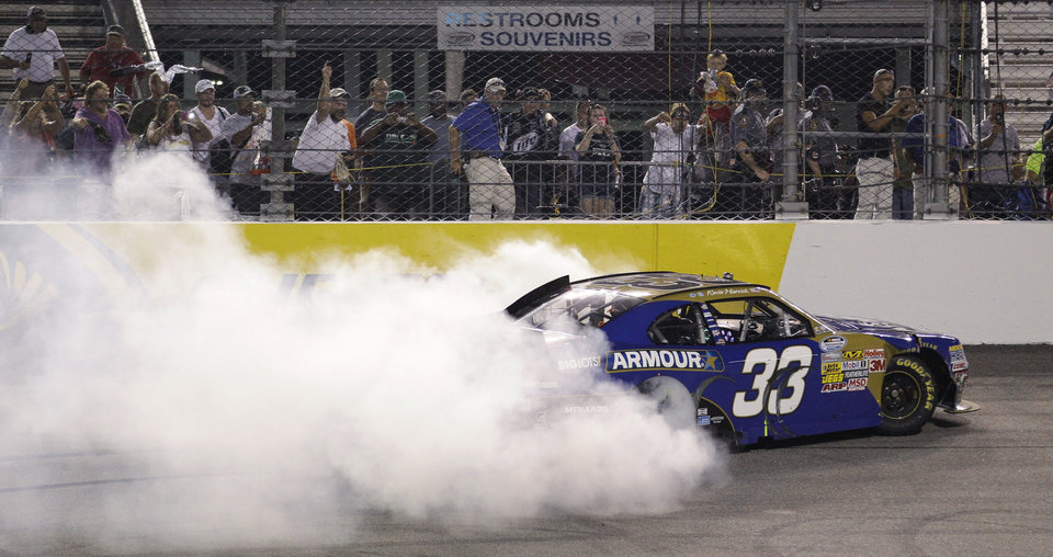 Photo -   Kevin Harvick does a burnout after winning the NASCAR Nationwide Series auto race at Richmond International Raceway in Richmond, Va., Friday, Sept. 7, 2012. (AP Photo/Steve Helber)