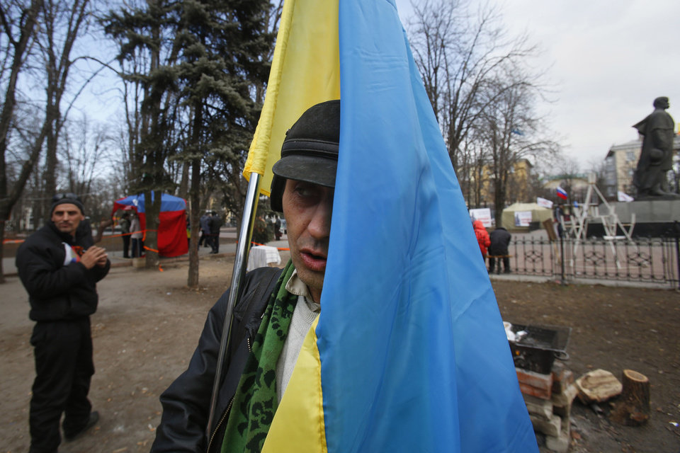Photo - In this photo taken Tuesday, March 11, 2014, pro Russian activists, one of them holding a Ukrainian flag, stand around a camp they set up in Luhansk, eastern Ukraine. In Ukraine's coal-fired industrial east, a potent mix of economic depression, ethnic solidarity and nostalgia for the certainties of the Soviet past among those old enough to remember them have many people demanding the right to become part of Russia as well. (AP Photo/Sergei Grits)