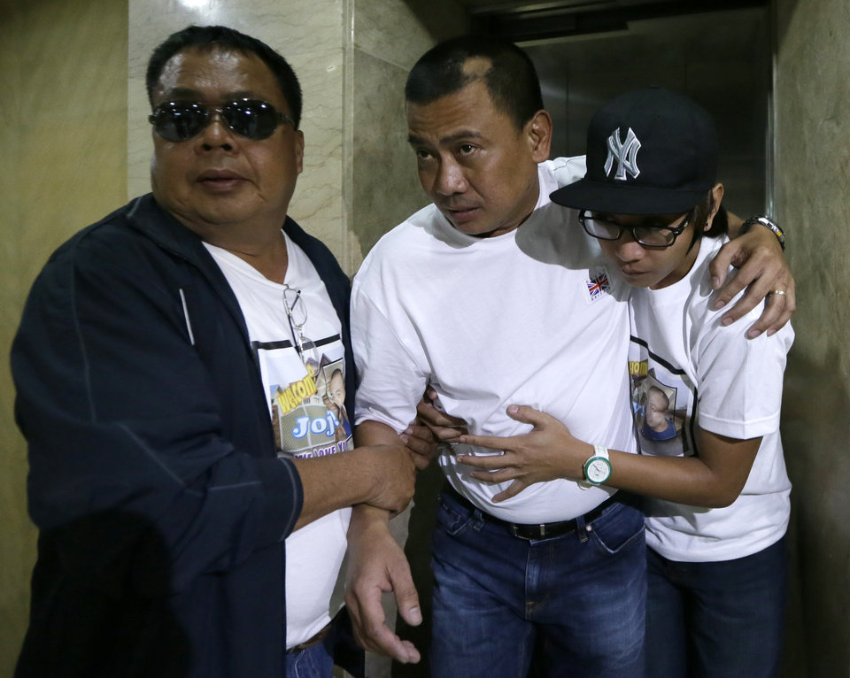 Photo - Joseph Balmaceda, center, one of the four Filipino oil field workers who was wounded but survived the terrorist attacks of an oil field in Algeria, limps to his waiting vehicle after talking to the media at the Overseas Workers Welfare Administration in Manila, Philippines, Monday Jan. 21, 2013.  In a separate briefing by the Department of Foreign Affairs, Spokesman Raul Hernandez said six Filipino workers were killed and four more are still unaccounted for. (AP Photo/Bullit Marquez)