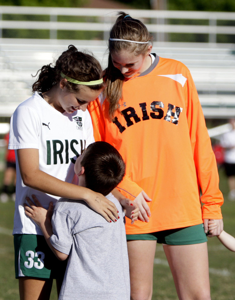 Photo - Nicole Voss and Elyse Hight, members fo the Bishop McGuiness High School girls' soccer team talk with Rob Medley, 6, before a soccer game at Bishop McGuinness on Tuesday.  SARAH PHIPPS - SARAH PHIPPS