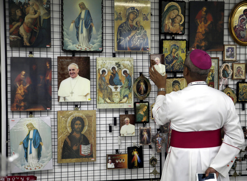 Photo - A Bishop holds a Pope Francis image sold in a shop of religious items during the Pontiff's visit at the Shrine of Haemi, in South Korea, Sunday, Aug. 17, 2014. (AP Photo/Gregorio Borgia)