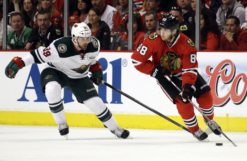 Photo - Chicago Blackhawks' Patrick Kane (88), right, controls the puck as he looks to a pass against Minnesota Wild's Nate Prosser (39) during the first period  in Game 2 of an NHL hockey second-round playoff series in Chicago, Sunday, May 4, 2014. (AP Photo/Nam Y. Huh)