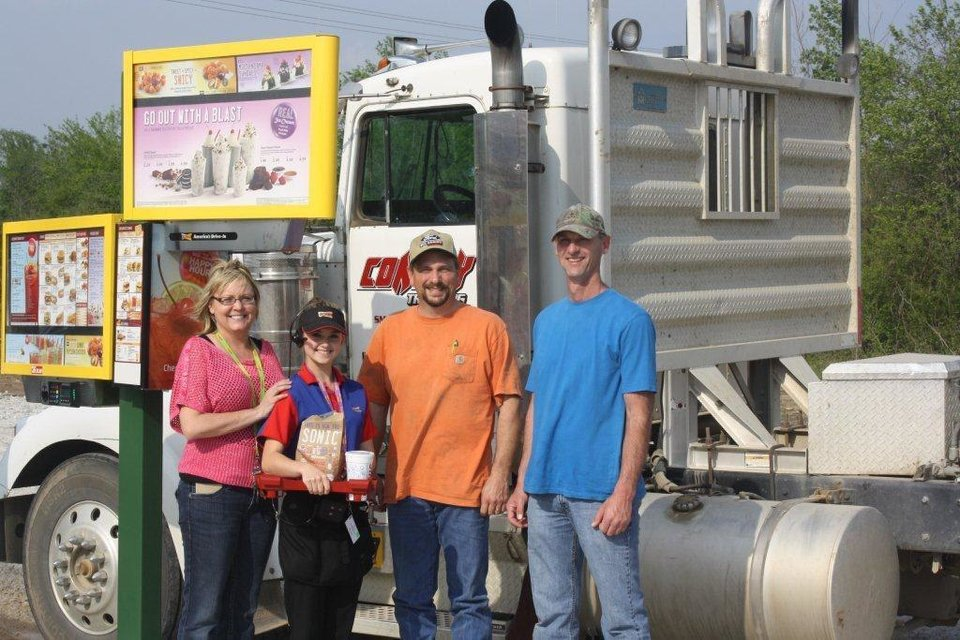 Photo - Sonic franchisees Julie Dorries (far left) and Tommy Dorries (far right), along with carhop Halee Elledge (second from left), greet a local guest as he pulls into the first Sonic Drive-In stall built for truck drivers.   - PROVIDED BY SONIC
