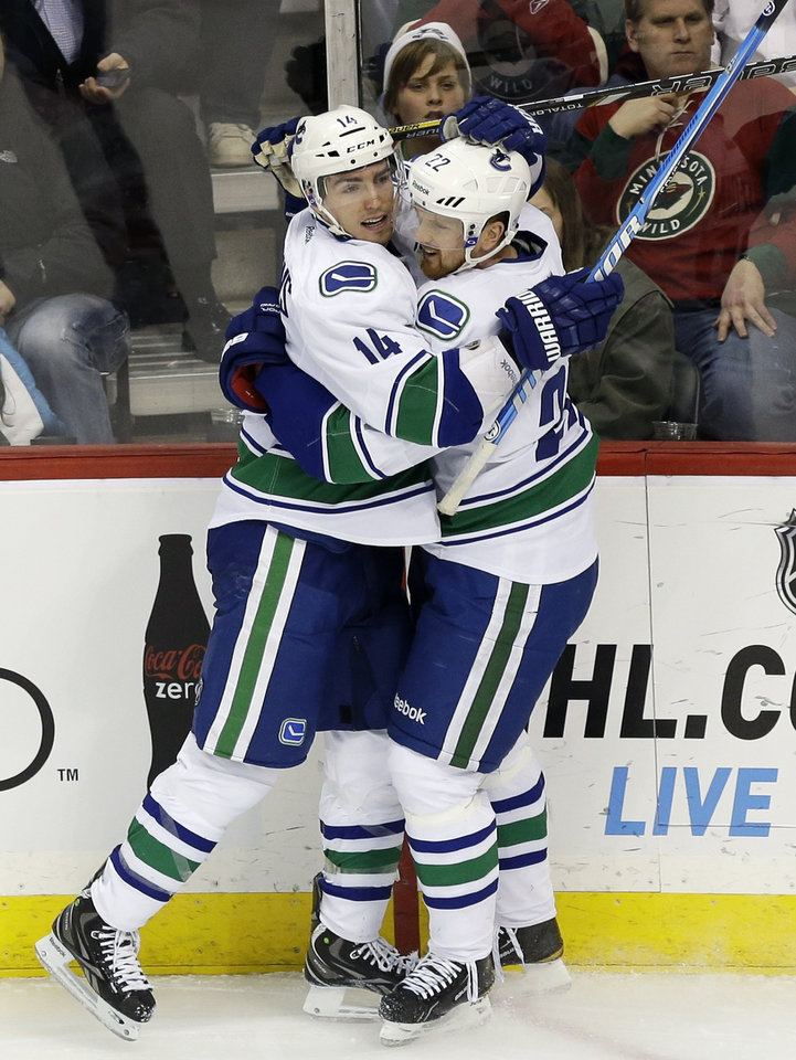 Vancouver Canucks' Alex Burrows , left, congratulates Vancouver Canucks' Daniel Sedin, of Sweden, after Sedin's goal off Minnesota Wild goalie Niklas Backstrom, of Finland, in the first period of an NHL hockey game on Thursday, Feb. 7, 2013, in St. Paul, Minn. (AP Photo/Jim Mone)