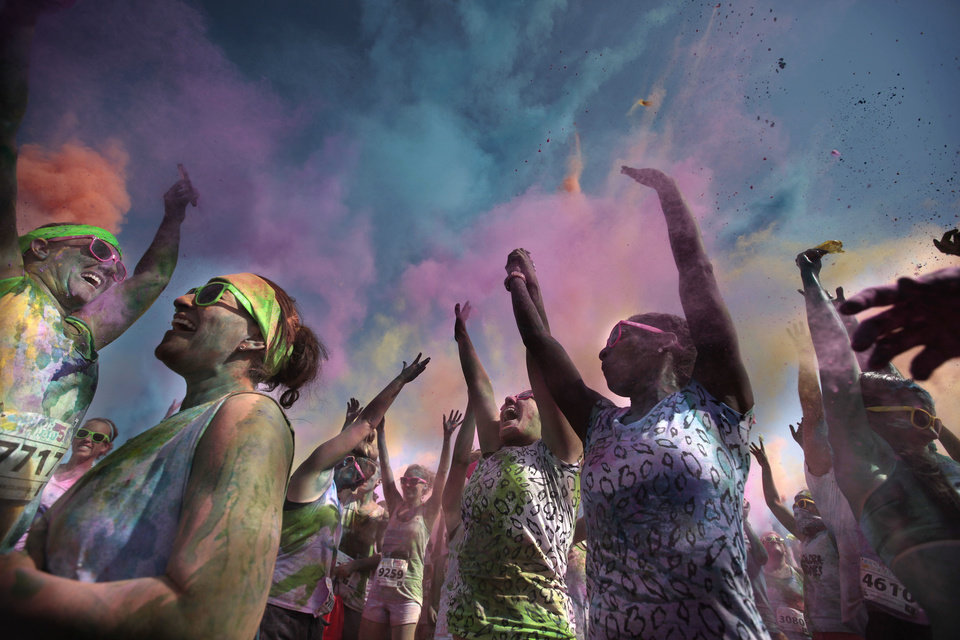 Photo - Runners celebrate finishing the Color Me Rad 5K race Saturday at State Fair Park in Oklahoma City. The race helped raise money for the Cystic Fibrosis Foundation. See more photos from the fundraiser on Page 7A. PHOTO BY SARAH PHIPPS, THE OKLAHOMAN