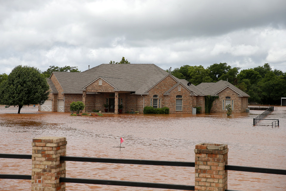 Photo - Floodwaters surround a home on Council just north of NW 164 in Oklahoma City, Tuesday, May 21, 2019. [Bryan Terry/The Oklahoman]