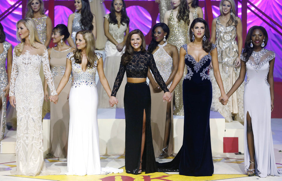 Photo -  The Miss Oklahoma finalists, from left, Miss Tulsa Sarah Klein, Miss Bricktown Jamie Butemeyer, Miss Okmulgee County Georgia Frazier, Miss Enid Alexandra Eppler, and Miss Oklahoma City Jordan E. Smith wait to hear who the winner is Saturday during the final round of the 2014 Miss Oklahoma Scholarship Pageant at the ORU Mabee Center in Tulsa.   JAMES GIBBARD -