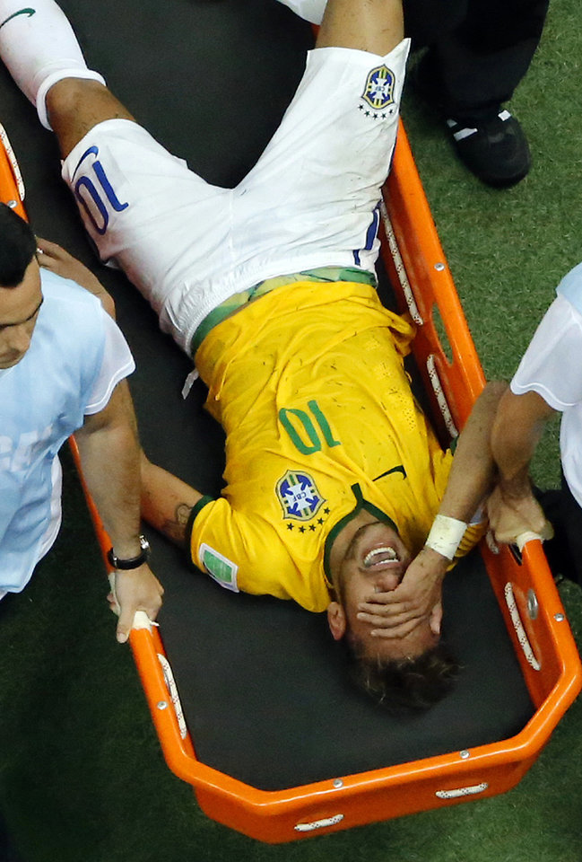 Photo - Brazil's Neymar is carried away after getting injured during the World Cup quarterfinal soccer match between Brazil and Colombia at the Arena Castelao in Fortaleza, Brazil, Friday, July 4, 2014. Brazil's team doctor says Neymar will miss the rest of the World Cup after breaking a vertebrae during the team's quarterfinal win over Colombia. (AP Photo/Fabrizio Bensch, pool)