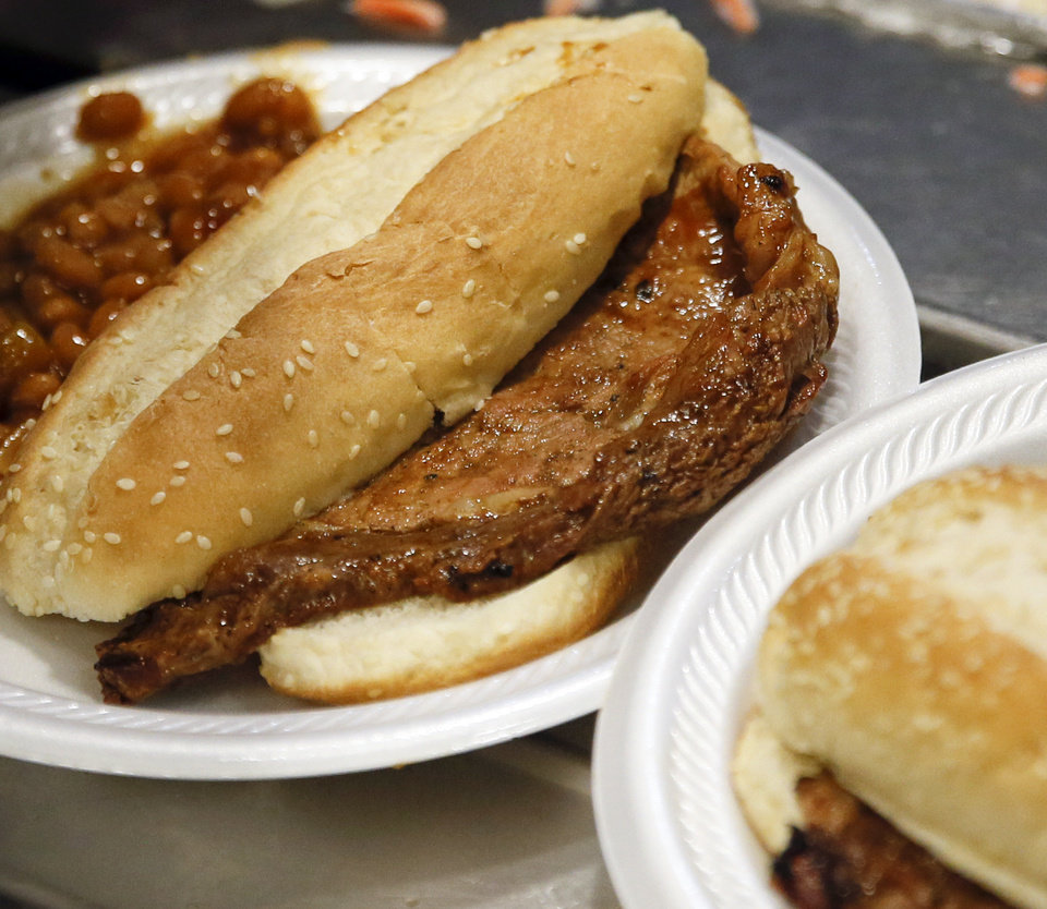 Photo -  Rib-eye steak sandwiches were served with main course at the Homeless Alliance's WestTown day shelter when the Oklahoma Cattlemen's Association and Beef Council served lunch on May 24. [Photo by Nate Billings, The Oklahoman]