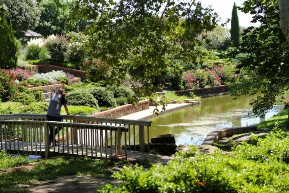 Photo -  A man  stops on a footbridge to enjoy a view at Will Rogers Gardens. [DOUG HOKE/THE OKLAHOMAN]