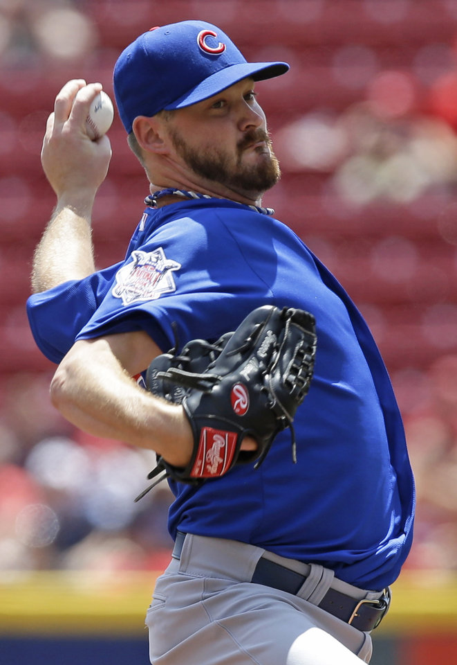 Photo - Chicago Cubs starting pitcher Travis Wood throws against the Cincinnati Reds in the first inning of a baseball game, Tuesday, July 8, 2014, in Cincinnati. (AP Photo/Al Behrman)