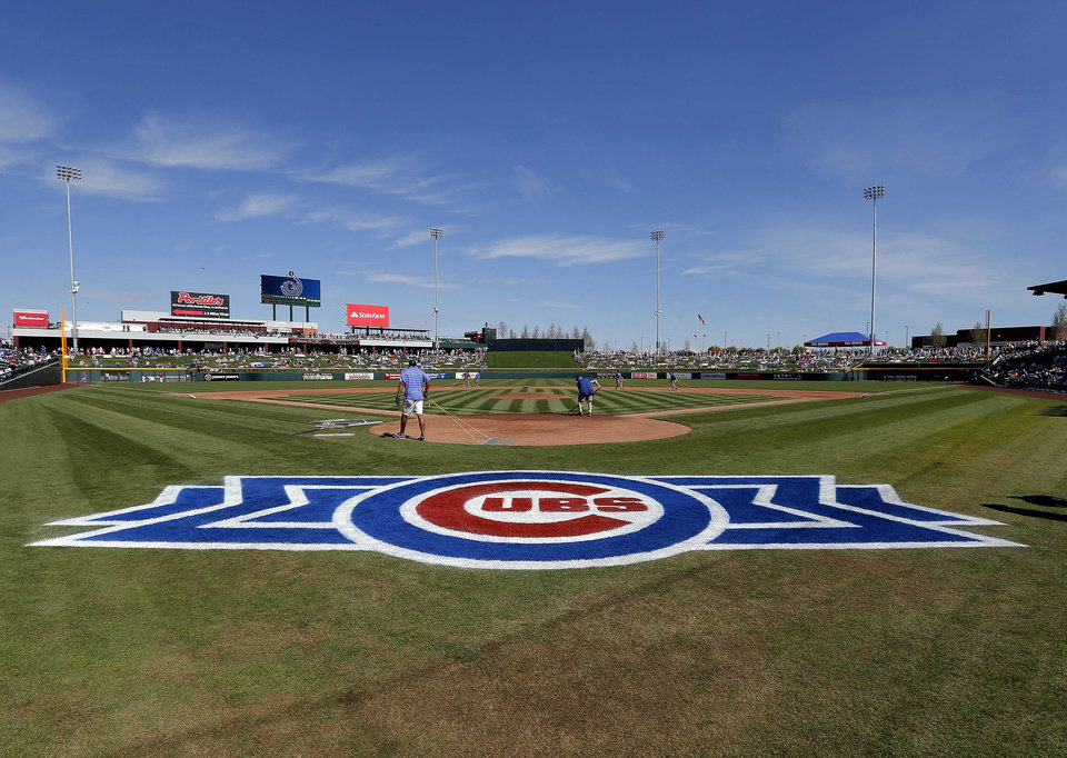 Photo - Grounds crew members prepare the infield before the Arizona Diamondbacks play the Chicago Cubs in a spring training baseball game on Thursday, Feb. 27, 2014, in Mesa, Ariz. It was the Cubs' first Cactus League game in their new spring training facility. (AP Photo/Matt York)
