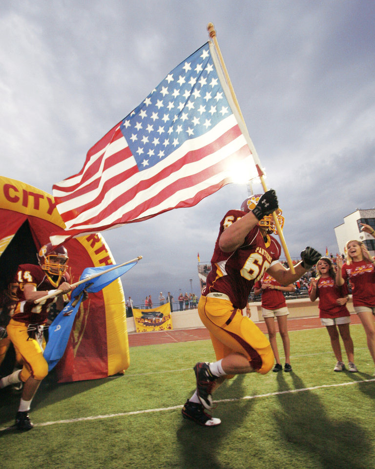 Photo - Putnam City North football player Dustin Decker runs onto the field carrying a flag on Sept. 11 in honor of those who died in the attacks. PHOTO BY RICHARD T. CLIFTON