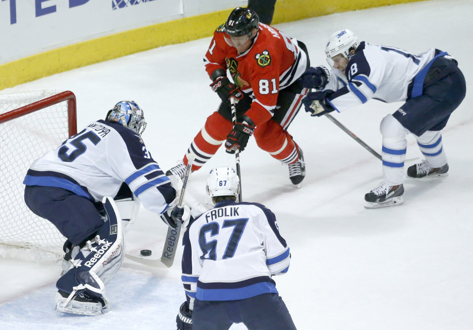 Photo - Winnipeg Jets goalie Al Montoya (35) makes a save on a shot by Chicago Blackhawks right wing Marian Hossa (81) as Michael Frolik (67) and James Wright defend during the first period of an NHL hockey game Sunday, Jan. 26, 2014, in Chicago. (AP Photo/Charles Rex Arbogast)