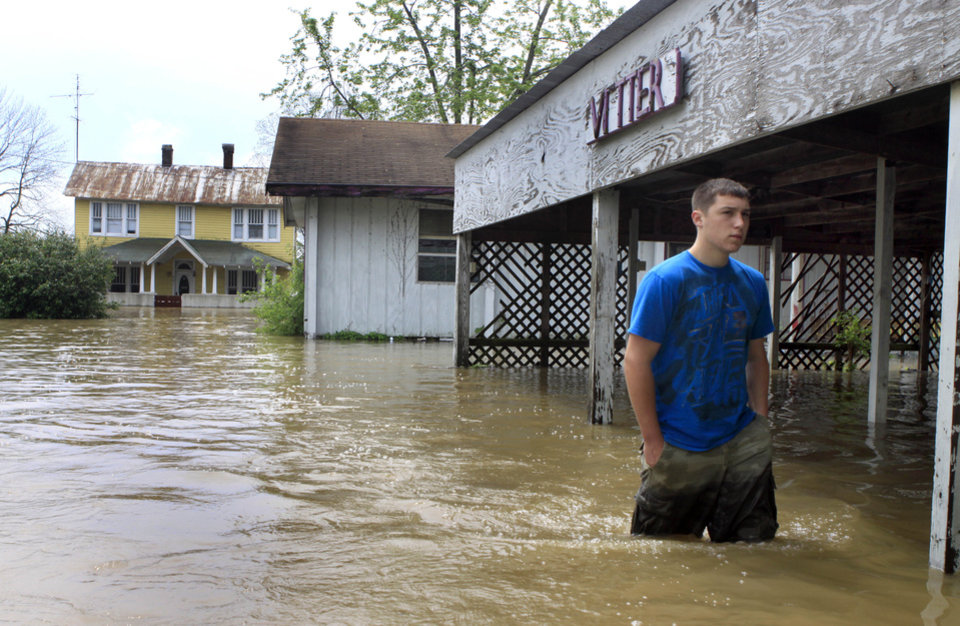 Photo - Zach Vetter walks in floodwater from the Mississippi River Wednesday, April 27, 2011, in Commerce, Mo. Powerful storms that swept through the nation's midsection have pushed river levels to dangerous heights and are threatening to flood several towns in Missouri. (AP Photo/Jeff Roberson)