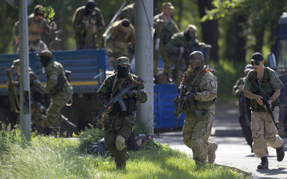 Photo - Pro-Russian insurgents arrive,  near the airport outside Donetsk, Ukraine, Monday, May 26, 2014. Ukraine's military launched airstrikes Monday against the separatists who had taken over the airport in the eastern city of Donetsk, suggesting that fighting in the east is far from over. (AP Photo/Vadim Ghirda)