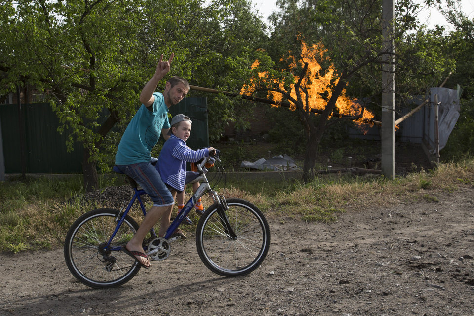 Photo - A local resident and his son ride a bicycle passing a flame from a damaged gas pipe after an impact of a mortar bomb, during fighting between Ukrainian government troops against pro-Russian militants, outside Slovyansk, eastern Ukraine, early Monday, May 19, 2014. Lawmakers and officials from eastern Ukraine on Saturday poured criticism on the fledging central government, accusing it of ignoring legitimate grievances of the regions which have been overrun by pro-Russia militia fighting for independence. (AP Photo/Alexander Zemlianichenko)