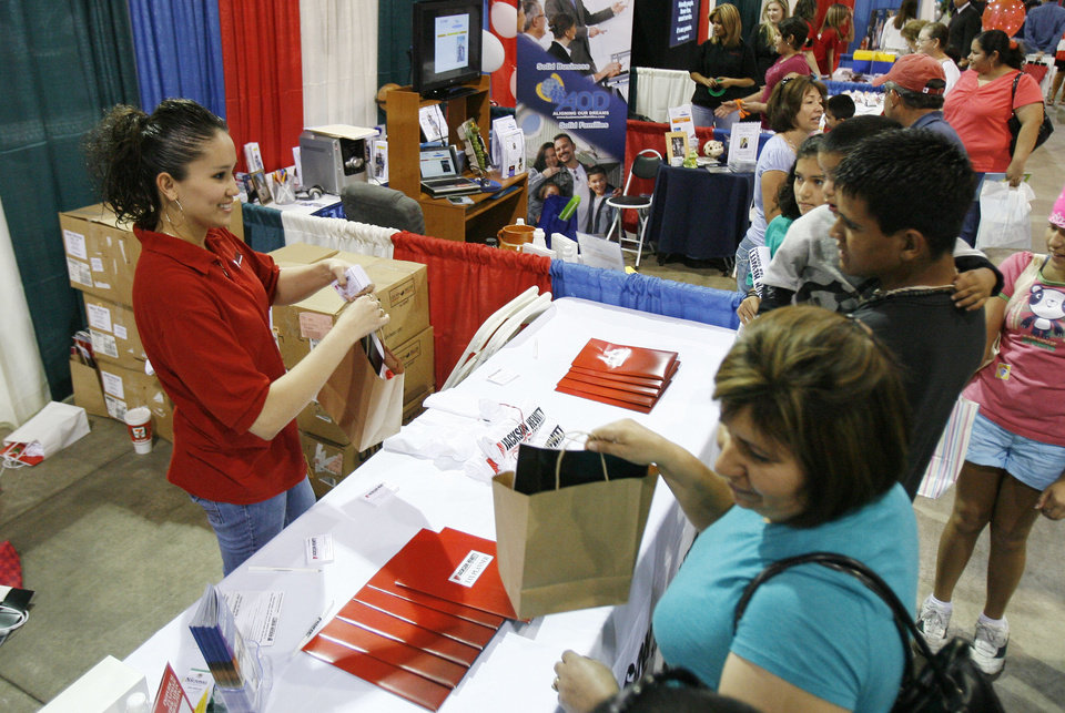 Yanet Gress passes out bags of goodies from the Jackson Hewitt Tax Services booth during the Viva Oklahoma Hispanic Chamber Expo and Career Fair at the State Fair Park Transportation Building in Oklahoma City, OK, Saturday, July 25, 2009. By Paul Hellstern, The Oklahoman